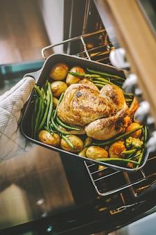 Cozinhe tomando frango pronto do forno