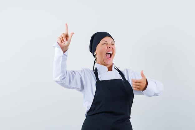 Cozinheira apontando para cima, aparecendo o polegar de uniforme, avental e parecendo louca, vista frontal.