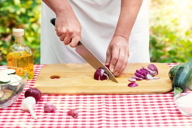 Cozinheira cortando cebolas vermelhas