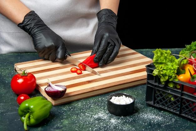 Cozinheira de frente cortando pimenta vermelha em um prato de comida cinza, cozinhando salada, cozinha, cozinha, refeição, tempero