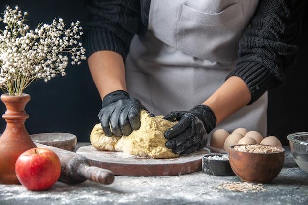 Cozinheira de frente, esticando a massa no trabalho de cozinha escura, pastelaria, bolo, ovo, massa