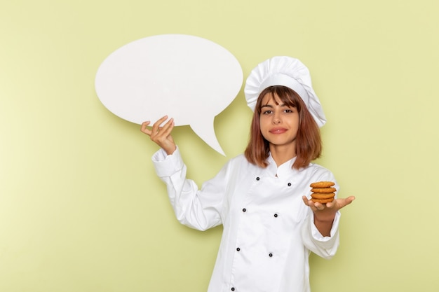 Cozinheira de frente para a cozinheira de terno branco segurando bolinhos e uma placa branca na superfície verde