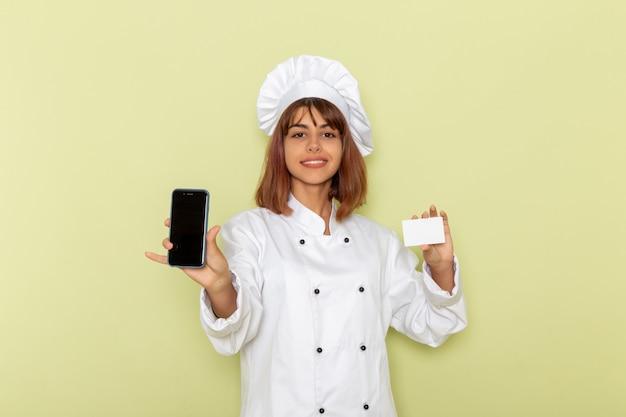 Cozinheira de frente para a cozinheira de terno branco segurando o cartão e o smartphone na superfície verde