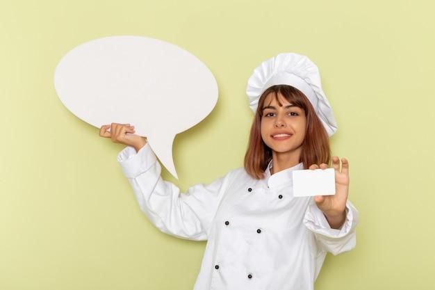 Cozinheira de frente para a cozinheira de terno branco segurando um cartão branco e uma placa em uma superfície verde