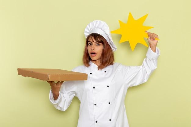 Cozinheira de frente para a cozinheira de terno branco segurando uma caixa de comida e uma placa amarela em uma superfície verde