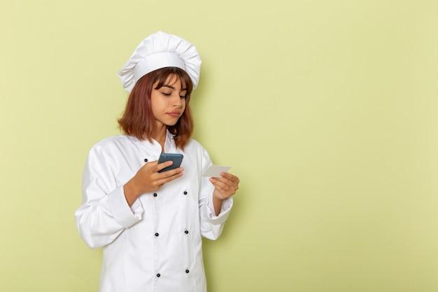 Cozinheira de frente para a cozinheira em um terno branco de cozinheira usando seu smartphone na superfície verde