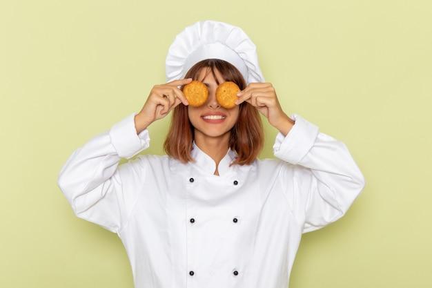 Cozinheira de frente para a cozinheira em um terno branco segurando biscoitos e sorrindo na superfície verde