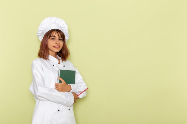 Cozinheira de frente para a cozinheira em um terno branco segurando um caderno verde na superfície verde