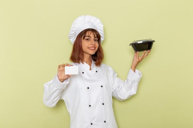 Cozinheira de frente para a cozinheira em um terno branco segurando um cartão branco e uma tigela na superfície verde