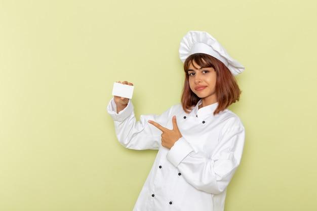 Cozinheira de frente para a cozinheira em um terno branco segurando um cartão branco na superfície verde