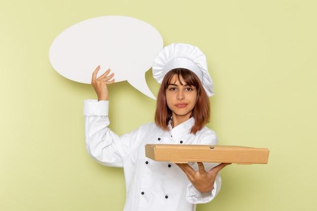 Cozinheira de frente para a cozinheira em um terno branco segurando uma caixa de comida e assinar na superfície verde