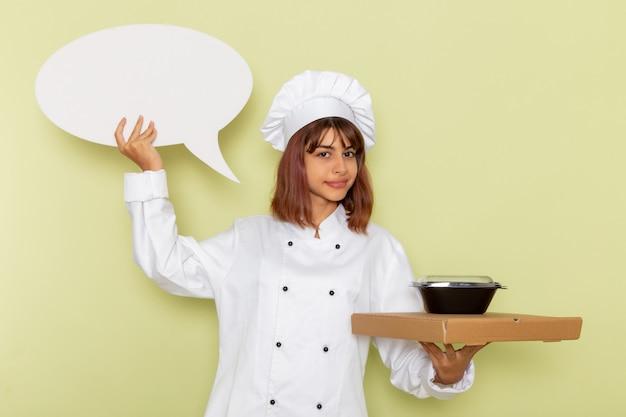 Cozinheira de frente para a cozinheira em um terno branco segurando uma caixa de comida e uma tigela preta na superfície verde clara