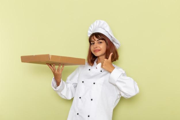 Cozinheira de frente para a cozinheira em um terno branco segurando uma caixa de comida na superfície verde