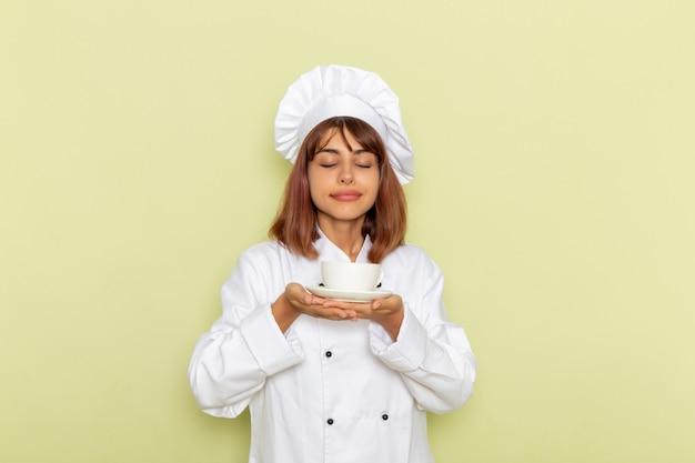 Cozinheira de frente para a cozinheira em um terno branco segurando uma xícara de chá em uma superfície verde clara