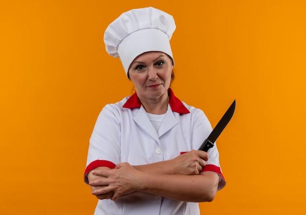 Cozinheira de meia-idade com uniforme de chef cruzando as mãos segurando uma faca na parede amarela isolada com espaço de cópia