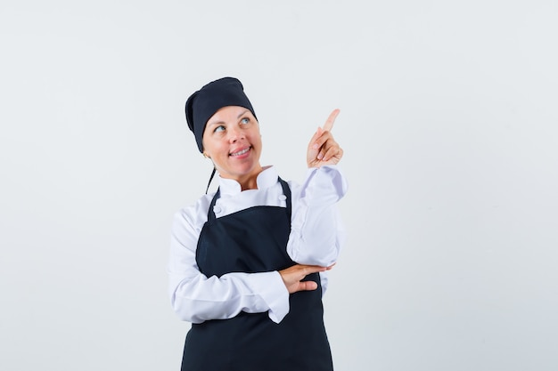 Cozinheira de uniforme, avental apontando para cima e parecendo um sonho, vista frontal.