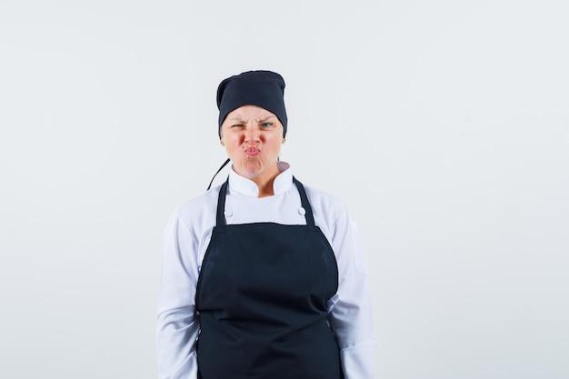 Cozinheira de uniforme, avental carrancudo enquanto olha para a câmera, vista frontal.