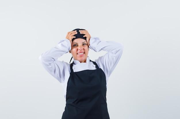 Cozinheira de uniforme, avental de mãos dadas na cabeça e olhando esquecido, vista frontal.