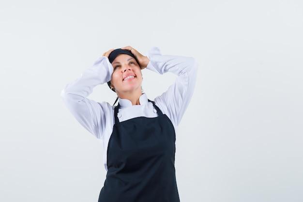Cozinheira de uniforme, avental de mãos dadas na cabeça e olhando feliz, vista frontal.