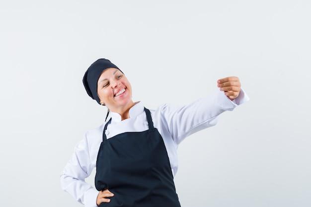 Cozinheira de uniforme, avental fingindo tirar selfie e olhando alegre, vista frontal.