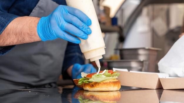 Cozinheira fazendo hambúrguer, adicionando molho, caminhão de comida