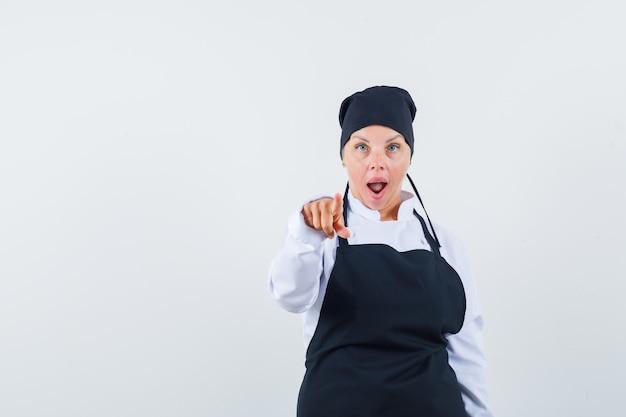 Cozinheira feminina, apontando para a câmera de uniforme, avental e olhando espantada, vista frontal.