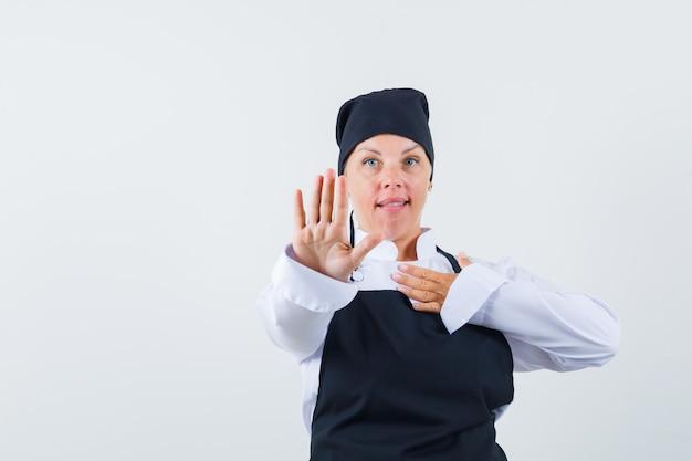 Cozinheira feminina mostrando gesto de parada no uniforme, avental e olhando cuidadosa, vista frontal.