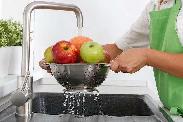 Cozinheira lava frutas em água corrente de uma torneira.