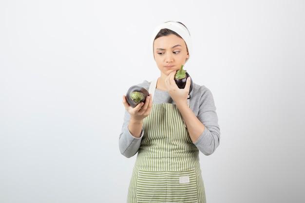 Cozinheira olhando berinjelas grandes em branco.