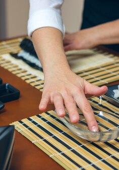 Cozinheira preparando sushi umedecendo a mão na água para fechar o maki roll