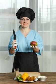 Cozinheira segura em uma mão uma fruta de manga e na outra mão uma faca.