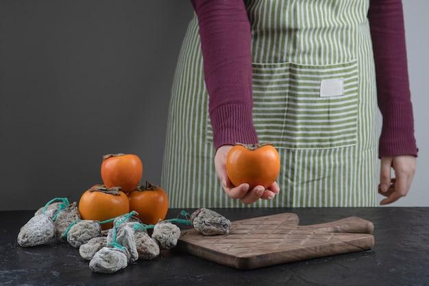 Cozinheira segurando uma única fruta de caqui na mesa preta