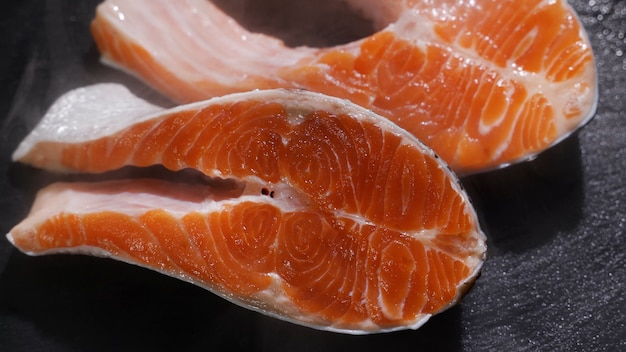 Cozinheira temperando bifes de salmão com pimenta preta na grelha