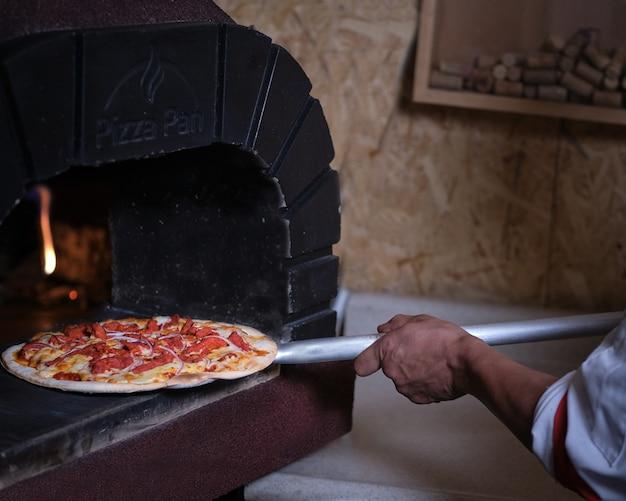 Cozinheira tirando pizza do forno de barro com chamas