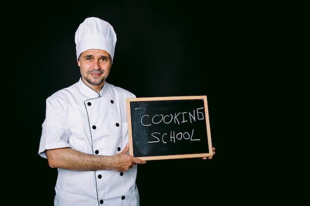 Cozinheira vestida com um chapéu branco e jaqueta segura uma lousa que diz: escola de culinária em um fundo preto. restaurante, comida e conceito de escola de culinária.