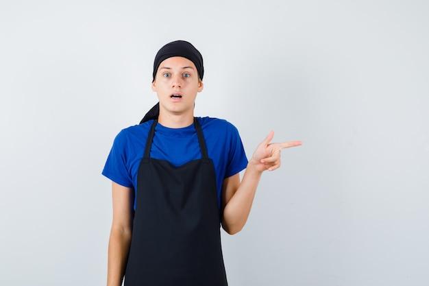 Cozinheiro adolescente masculino apontando para o lado direito em t-shirt, avental e olhando surpreso, vista frontal.