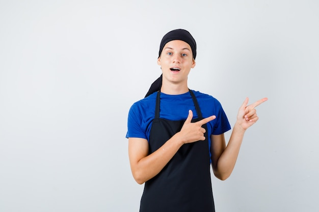 Cozinheiro adolescente masculino em t-shirt, avental apontando para o lado direito, abrindo a boca e olhando espantado, vista frontal.