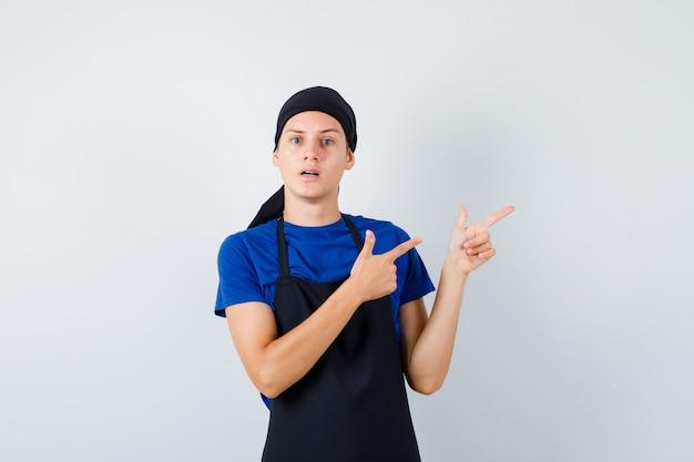 Cozinheiro adolescente masculino em t-shirt, avental apontando para o lado direito e parecendo desnorteado, vista frontal.