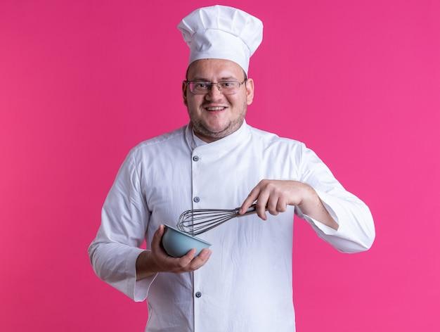 Cozinheiro adulto alegre do sexo masculino usando uniforme de chef e óculos segurando um batedor e uma tigela, olhando para a câmera isolada no fundo rosa