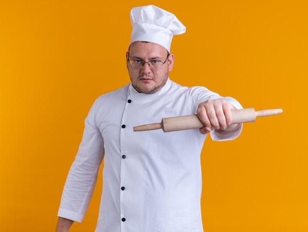 Cozinheiro adulto confiante usando uniforme de chef e óculos, olhando para a câmera, esticando o rolo de massa em direção à câmera, isolada em um fundo laranja