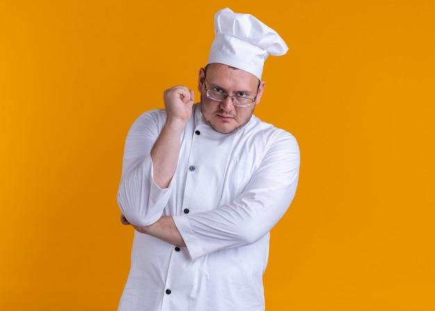 Cozinheiro adulto confiante usando uniforme de chef e óculos olhando para a frente, mantendo a mão sob o cotovelo e o punho no ar isolado na parede laranja com espaço de cópia