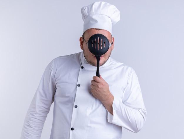 Cozinheiro adulto impressionado usando uniforme de chef e óculos segurando uma escumadeira na frente do rosto através dela isolada na parede branca