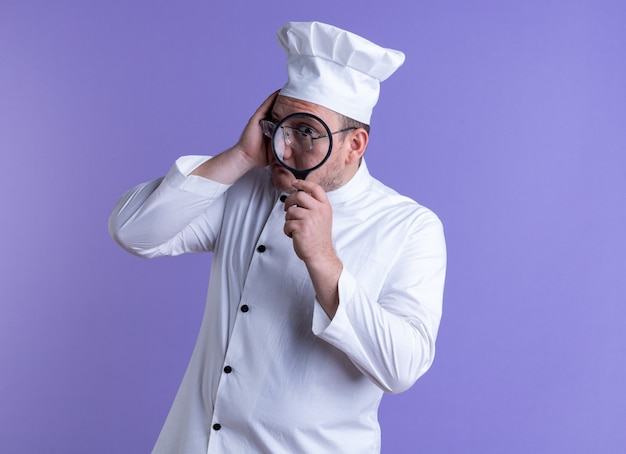 Cozinheiro adulto impressionado usando uniforme de chef e óculos tocando a cabeça, olhando para a câmera através de lupas isoladas em um fundo roxo com espaço de cópia