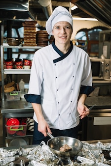 Cozinheiro alegre fritar a carne na panela no fogão