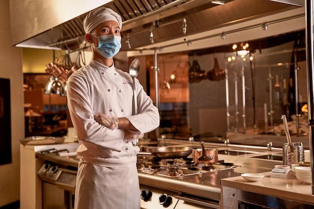 Cozinheiro asiático cruzando os braços e olhando à distância