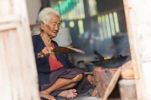 Cozinheiro asiático sênior do cozinheiro chefe da mulher na cozinha.