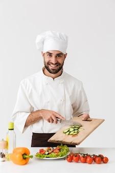 Cozinheiro bonito homem de uniforme sorrindo e cortando salada de legumes na placa de madeira isolada sobre a parede branca