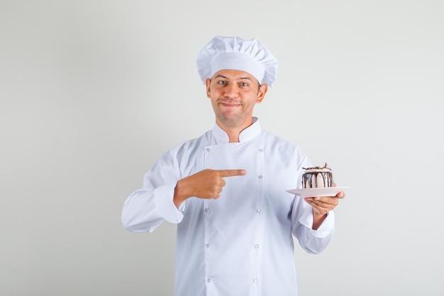 Cozinheiro chef masculino apontando o dedo indicador no bolo de chapéu e uniforme