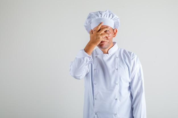 Cozinheiro chef masculino, cobrindo um olho com a mão no chapéu e uniforme