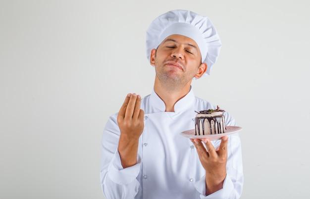 Cozinheiro chef masculino segurando o bolo e fazendo gesto italiano no chapéu e uniforme